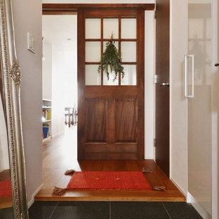 引き戸カントリー風おしゃれな玄関ホール (白い壁、木目調のドア) の写真