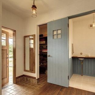他の地域の片開きドアカントリー風おしゃれな玄関 (白い壁、テラコッタタイルの床、木目調のドア、茶色い床) の写真