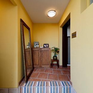 他の地域の北欧スタイルのおしゃれな玄関 (黄色い壁、ベージュの床) の写真