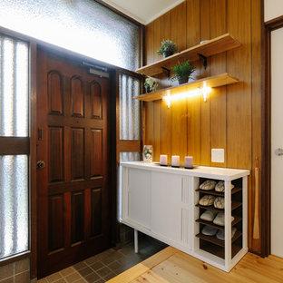 他の地域の小さい片開きドア和風のおしゃれな玄関ホール (茶色い壁、淡色無垢フローリング、濃色木目調のドア、ベージュの床) の写真
