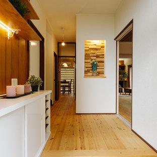 Idée de décoration pour une petite entrée asiatique avec un couloir, un mur blanc, un sol en bois brun, une porte simple, une porte en bois foncé et un sol marron.