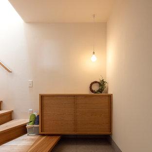 他の地域の片開きドアアジアンスタイルのおしゃれな玄関 (白い壁、グレーの床、下駄箱) の写真