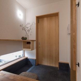 Modelo de entrada de estilo zen con paredes blancas, puerta simple, puerta de madera clara y suelo negro