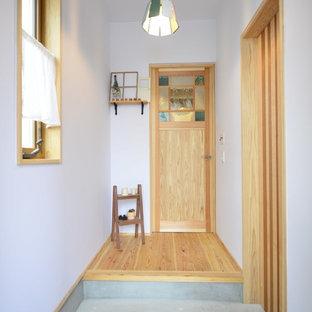 他の地域のコンテンポラリースタイルのおしゃれな玄関 (白い壁、コンクリートの床、グレーの床) の写真