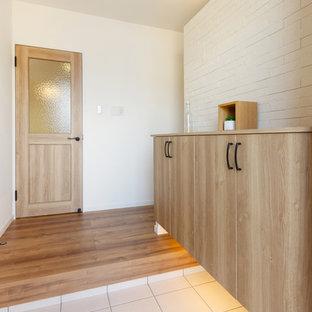 他の地域の北欧スタイルのおしゃれな玄関 (白い壁、無垢フローリング、茶色い床) の写真