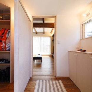他の地域のモダンスタイルのおしゃれな玄関ホール (白い壁、黒い床) の写真