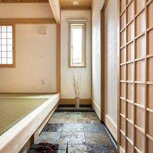 Удачное сочетание для дизайна помещения: узкая прихожая в восточном стиле с белыми стенами, раздвижной входной дверью, входной дверью из светлого дерева и серым полом - самое интересное для вас