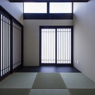 Cette photo montre une entrée asiatique avec un mur blanc, une porte coulissante, un sol de tatami et un couloir.