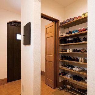 横浜の片開きドアトラディショナルスタイルのおしゃれな玄関 (白い壁、テラコッタタイルの床、黒いドア、茶色い床) の写真