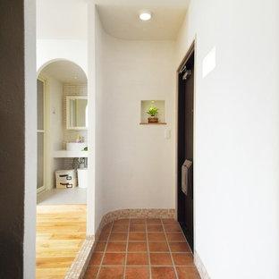 他の地域の片開きドア地中海スタイルのおしゃれな玄関ホール (白い壁、テラコッタタイルの床、黒いドア、茶色い床) の写真