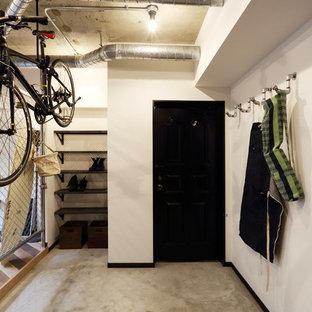 東京23区の中サイズの片開きドアインダストリアルスタイルのおしゃれな玄関ホール (無垢フローリング) の写真