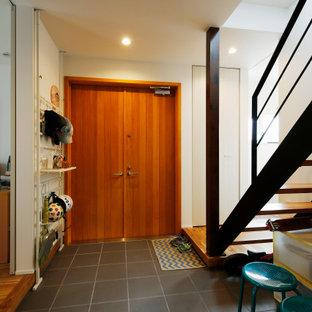 Bild på ett mellanstort industriellt kapprum, med vita väggar, klinkergolv i porslin, en dubbeldörr, mellanmörk trädörr och grått golv