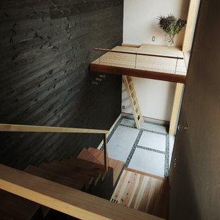 他の地域のインダストリアルスタイルのおしゃれな玄関ホール (黒い壁、コンクリートの床) の写真