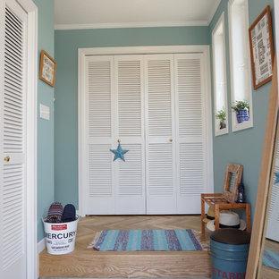 他の地域のトロピカルスタイルのおしゃれな玄関 (青い壁、コンクリートの床) の写真