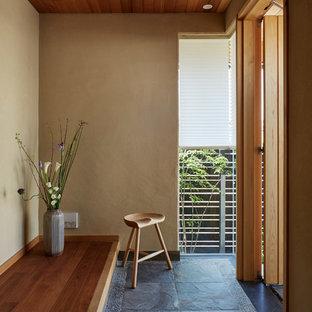 他の地域の片開きドアコンテンポラリースタイルのおしゃれな玄関ホール (茶色い壁、木目調のドア、グレーの床) の写真