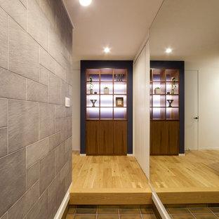 大阪のインダストリアルスタイルのおしゃれな玄関ホール (マルチカラーの壁、茶色い床) の写真