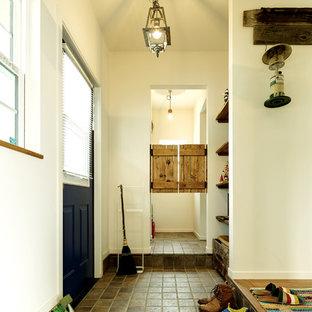 Ispirazione per un corridoio stile marinaro di medie dimensioni con pareti bianche, pavimento in terracotta, una porta singola, una porta blu e pavimento beige