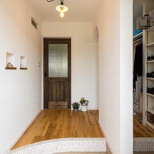 他の地域のカントリー風おしゃれな玄関 (白い壁、セラミックタイルの床、ベージュの床) の写真