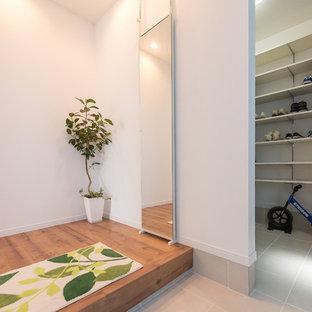 Cette image montre une porte d'entrée minimaliste de taille moyenne avec un mur blanc, un sol en contreplaqué, une porte simple et un sol marron.