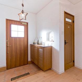 他の地域の片開きドアカントリー風おしゃれな玄関 (白い壁、テラコッタタイルの床、木目調のドア、オレンジの床) の写真