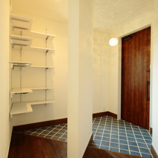 Cette image montre une entrée avec un mur blanc, un sol en carreau de terre cuite, une porte simple, une porte en bois foncé, un sol turquoise, un plafond en papier peint et du papier peint.
