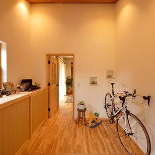 他の地域の片開きドア北欧スタイルのおしゃれな玄関ホール (ベージュの壁、淡色無垢フローリング、茶色い床) の写真