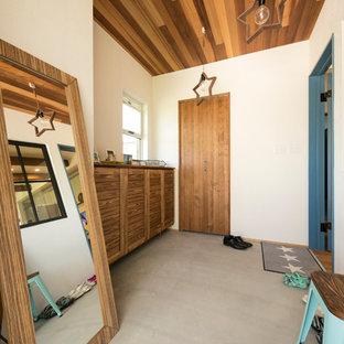 他の地域のビーチスタイルのおしゃれな玄関ホール (白い壁、コンクリートの床、グレーの床) の写真