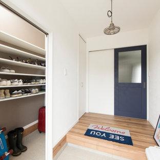 Inredning av en hall, med vita väggar, plywoodgolv och brunt golv