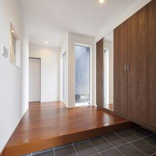 Cette image montre une entrée minimaliste avec un couloir, un mur blanc, un sol gris, un plafond en papier peint et du papier peint.
