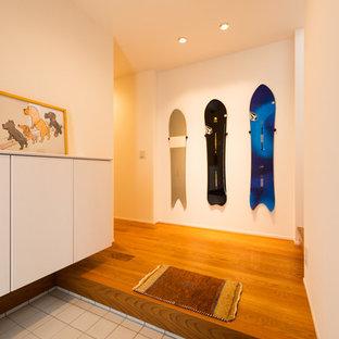 他の地域のモダンスタイルのおしゃれな玄関 (白い壁、グレーの床) の写真