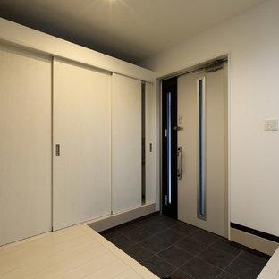 Imagen de puerta principal minimalista, de tamaño medio, con paredes blancas, suelo de baldosas de porcelana, puerta simple, puerta blanca y suelo negro