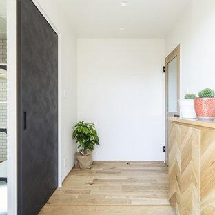 他の地域の中サイズの片開きドアモダンスタイルのおしゃれな玄関ロビー (白い壁、淡色無垢フローリング、茶色いドア、茶色い床) の写真