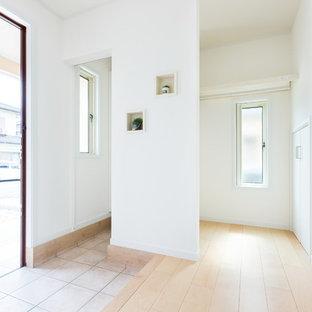 Неиссякаемый источник вдохновения для домашнего уюта: узкая прихожая в стиле модернизм с белыми стенами, полом из фанеры, одностворчатой входной дверью, входной дверью из темного дерева и бежевым полом