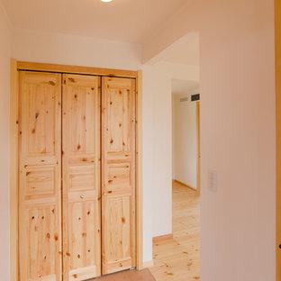 Foto di una piccola porta d'ingresso nordica con pareti bianche, pavimento in terracotta, una porta singola, una porta in legno bruno e pavimento rosa