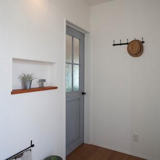 Foto på en skandinavisk hall, med vita väggar, plywoodgolv, en enkeldörr, mellanmörk trädörr och brunt golv