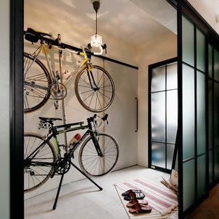 他の地域の引き戸インダストリアルスタイルのおしゃれな玄関 (白い壁、コンクリートの床、グレーのドア、グレーの床) の写真