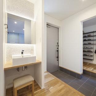Imagen de entrada urbana con paredes blancas, puerta simple, puerta metalizada y suelo negro