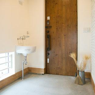 他の地域の大きい片開きドアコンテンポラリースタイルのおしゃれな玄関 (白い壁、コンクリートの床、木目調のドア、グレーの床) の写真