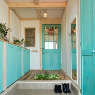 他の地域の地中海スタイルのおしゃれな玄関ホール (白い壁、ベージュの床) の写真