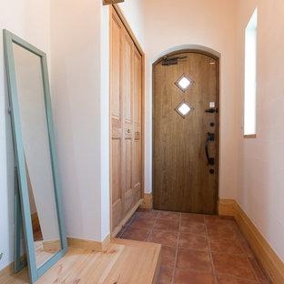 他の地域の片開きドアアジアンスタイルのおしゃれな玄関ホール (白い壁、テラコッタタイルの床、木目調のドア、オレンジの床) の写真