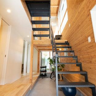 Foto di un piccolo ingresso con anticamera industriale con pareti marroni, pavimento in cemento, pavimento grigio, soffitto in carta da parati e pareti in legno