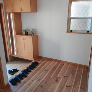 Idee per un corridoio tradizionale con pareti marroni, pavimento in compensato e pavimento marrone