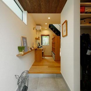 東京23区の中くらいの片開きドア北欧スタイルのおしゃれなマッドルーム (白い壁、コンクリートの床、木目調のドア、グレーの床) の写真