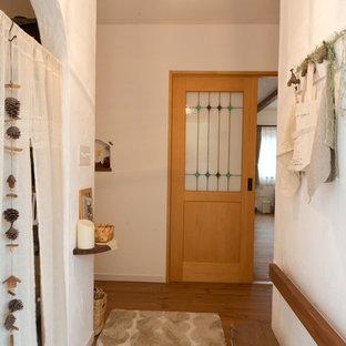 Inspiration för lantliga entréer, med vita väggar, klinkergolv i terrakotta, mellanmörk trädörr och orange golv