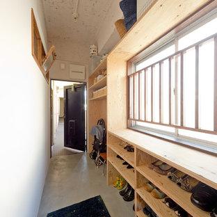 大阪の片開きドアアジアンスタイルのおしゃれな玄関ホール (白い壁、コンクリートの床、グレーの床、黒いドア) の写真