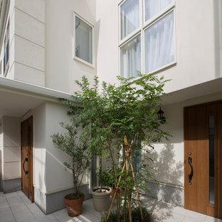Idéer för mellanstora vintage ingångspartier, med beige väggar, terrazzogolv, ljus trädörr och vitt golv