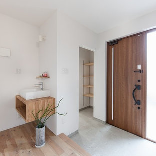 Inspiration for an asian entry hall in Other with white walls, concrete floors, a single front door, a medium wood front door and grey floor.
