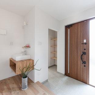 Пример оригинального дизайна: узкая прихожая в восточном стиле с белыми стенами, бетонным полом, одностворчатой входной дверью, входной дверью из дерева среднего тона и серым полом