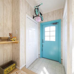 他の地域の片開きドアビーチスタイルのおしゃれな玄関ホール (ベージュの壁、青いドア、グレーの床) の写真