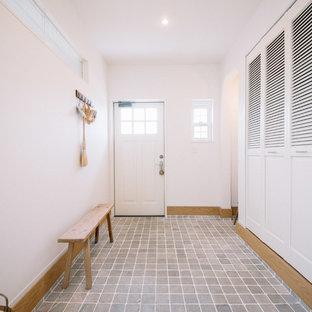 他の地域の片開きドアトラディショナルスタイルのおしゃれな玄関ホール (白い壁、磁器タイルの床、白いドア、グレーの床) の写真